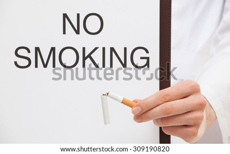 """Doctor holding a clipboard with text """"No smoking"""" and broken cigarette, white background - stock photo"""