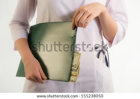 Doctor holding a folder with documents which show the money - stock photo