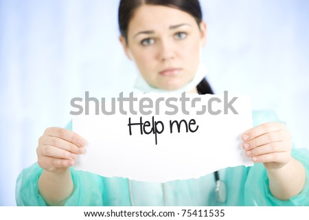 Doctor holding a paper sign with a message - stock photo