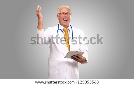 Doctor Holding A Tablet And Happy On gray Background - stock photo