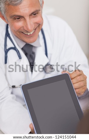Doctor holding a tablet computer while smiling in medical office - stock photo