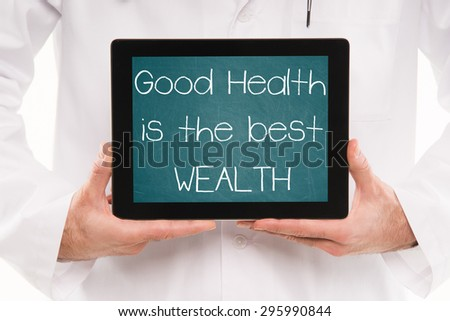 Doctor holding a tablet pc with GOOD HEALTH is the BEST WEALTH text on a green chalkboard screen. - stock photo