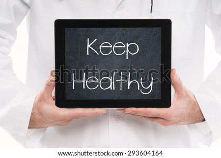 Doctor holding a tablet pc with KEEP HEALTHY text on a black Chalkboard screen. - stock photo