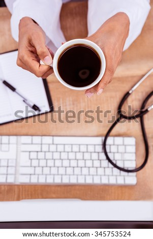 Doctor holding black coffee cup on desk - stock photo