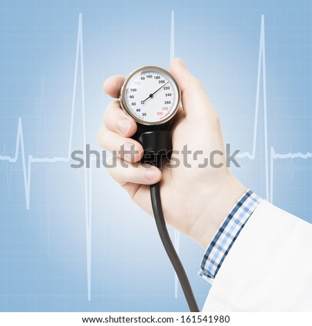 Doctor holding blood pressure measuring tool on blue background - studio shot - stock photo
