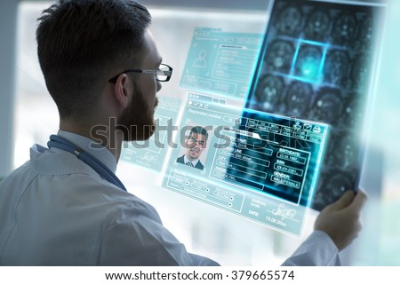 Doctor holding brain mri and examining it using virtual future technology - stock photo