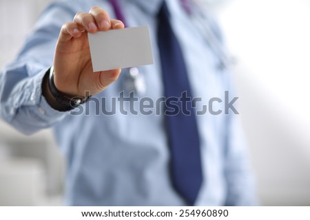Doctor holding business card - stock photo