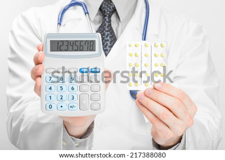 Doctor holding calculator and pills in his hands - health care concept - stock photo