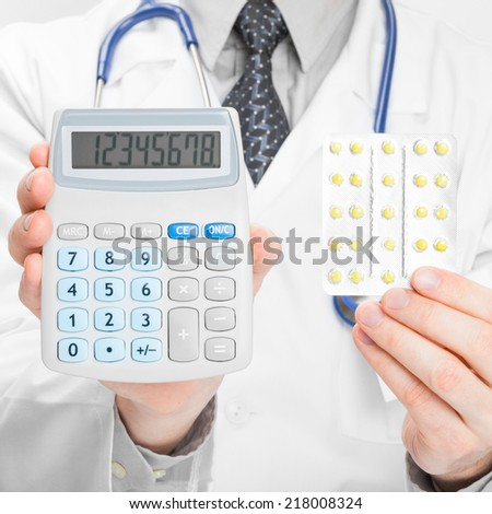 Doctor holding calculator and pills in his hands - heath care concept - 1 to 1 ratio - stock photo