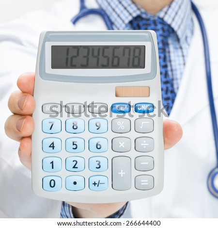 Doctor holding calculator in hand - health care concept - studio shot - stock photo