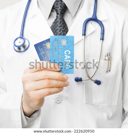 Doctor holding credit cards - 1 to 1 ratio - stock photo