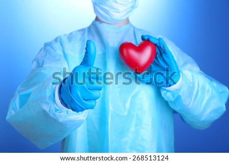 Doctor holding decorative heart on blue background