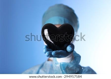 Doctor holding decorative heart on blue background - stock photo