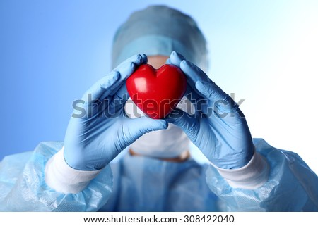Doctor holding decorative heart on blue background - stock photo