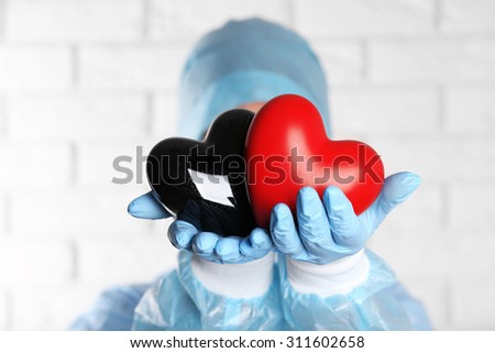 Doctor holding decorative hearts on brick wall background - stock photo