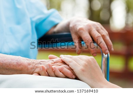 Doctor holding elderly patient 's hand in a wheelchair. - stock photo