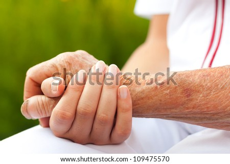 Doctor holding hand of an elderly woman - stock photo