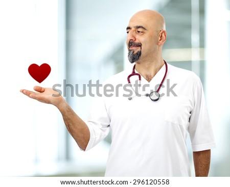 Doctor holding heart shape - stock photo