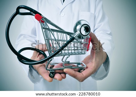doctor holding in his hand a shopping cart with a stethoscope inside, depicting the health care industry concept - stock photo