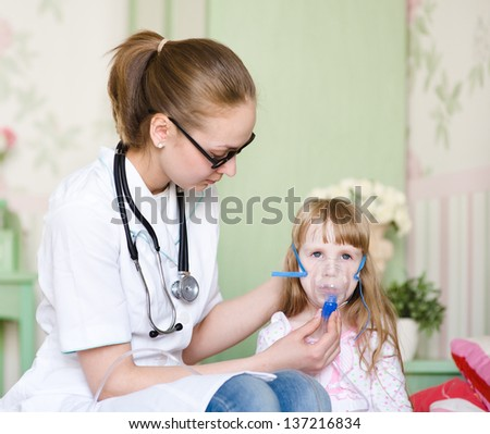 Doctor holding inhaler mask for kid breathing - stock photo