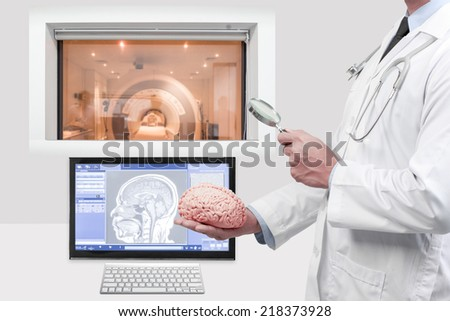 doctor holding magnifying for searching the brain at magnetic resonance image (MRI) of the brain on screen for diagnosis in operation room  - stock photo