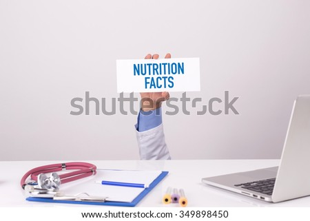 Doctor Holding Placard written NUTRITION FACTS - stock photo