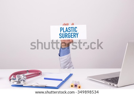 Doctor Holding Placard written PLASTIC SURGERY