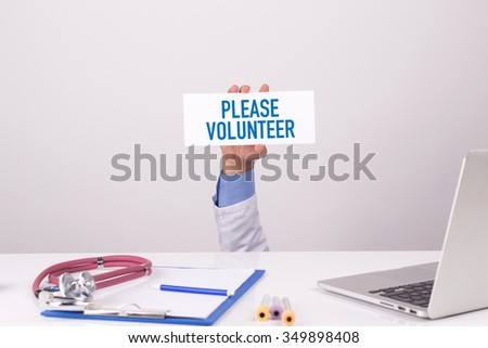 Doctor Holding Placard written PLEASE VOLUNTEER