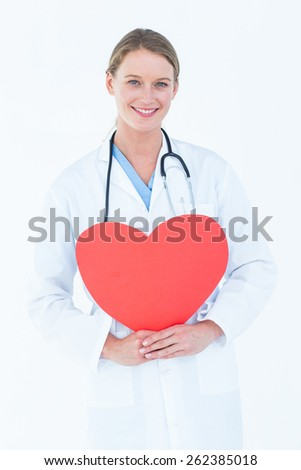 Doctor holding red heart card on white background - stock photo