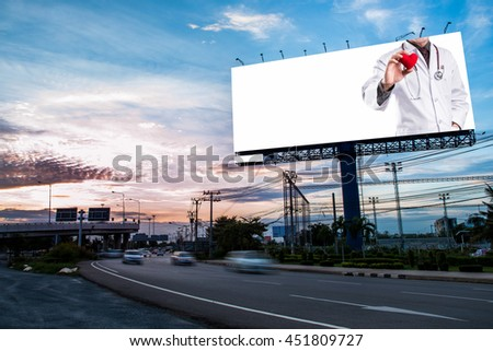 doctor holding red heart shape on blank billboard for advertisement at twilight time.