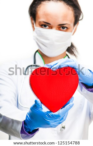 Doctor holding red heart symbol on white background - stock photo