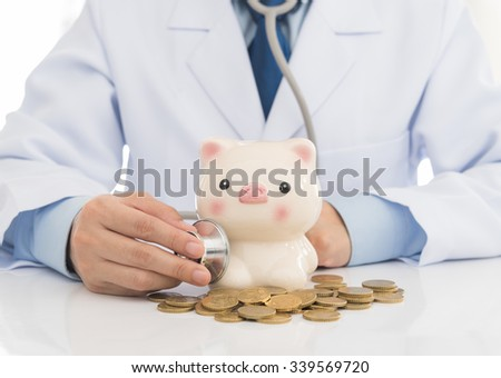 Doctor holding stethoscope touch to piggy bank. Concept for healthcare insurance fees and financial health check. - stock photo