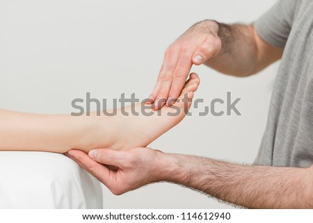 Doctor holding the foot of a patient in a room