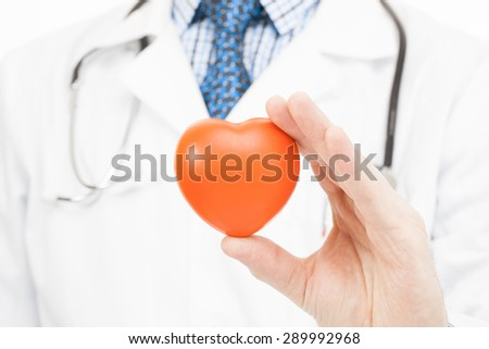 Doctor holding toy heart in his left hand - health care concept - stock photo