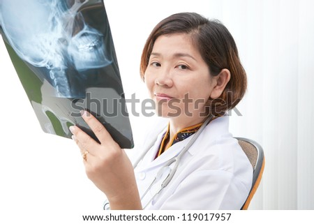 doctor holding x-ray film of head skull watching to camera