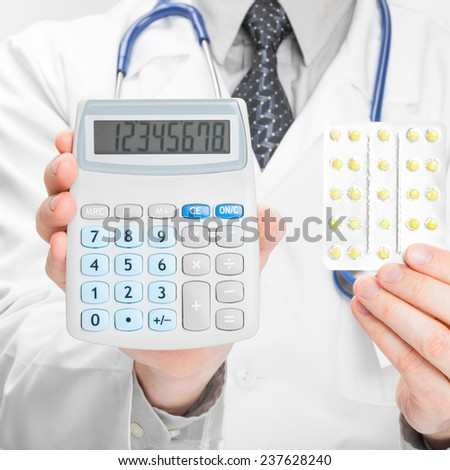 Doctor holdling calculator and pills in his hands - medical aid concept - stock photo