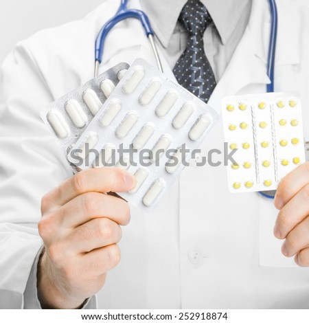 Doctor holdling pills in two hands - heath care concept - stock photo