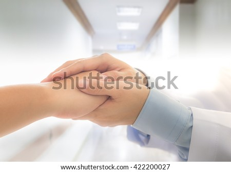 Doctor holing patient's hands and comforting or encouraging her. Medical concept.