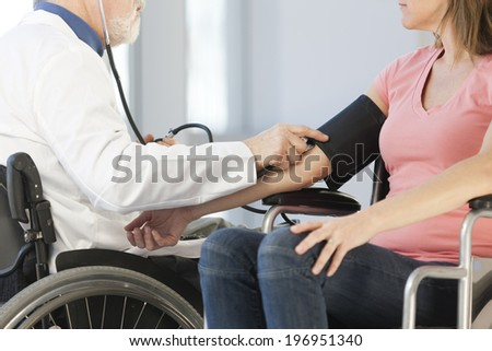Doctor in a wheelchair taking the blood pressure of a female patient - stock photo