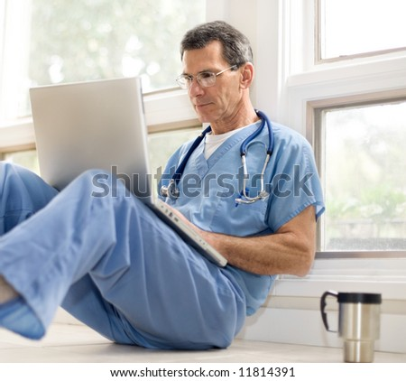 Doctor in blue scrubs relaxing with his laptop on coffee break. Selective focus. - stock photo