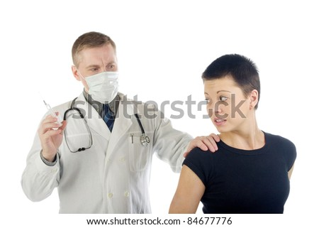 Doctor in gauze mask holds a frightened woman by her shoulder and prepares a syringe for an injection
