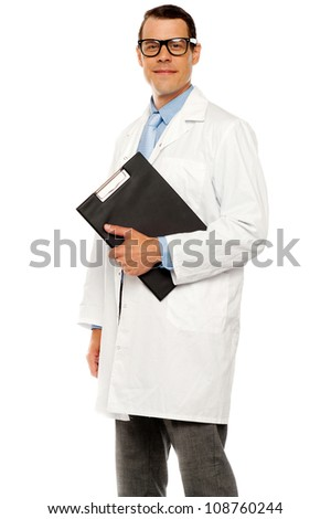 Doctor in glasses carrying clipboard on white background - stock photo