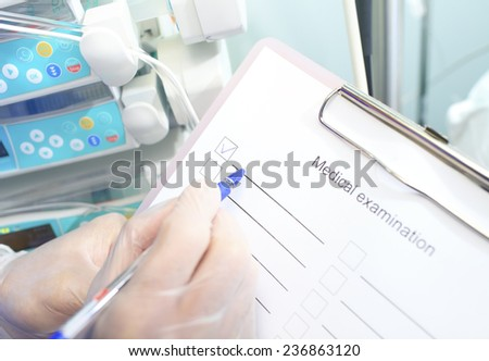 Doctor in gloves makes notes in the list - stock photo