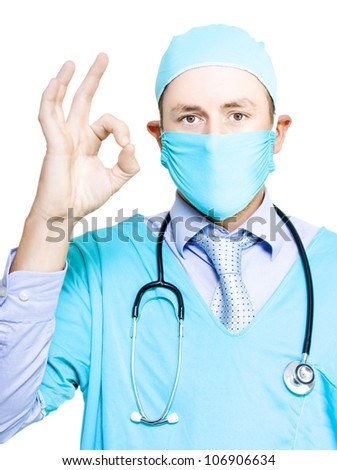 Doctor in gown and mask giving a gesture of perfection to confirm that his patient is in excellent heath isolated on white