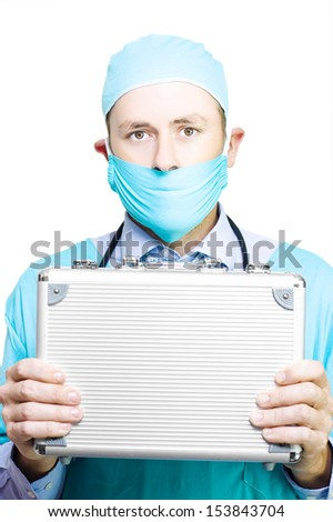 Doctor in mask and gown holding a metal first aid kit as he extols the virtues of having a sturdy allweather medical container in case of emergencies - stock photo