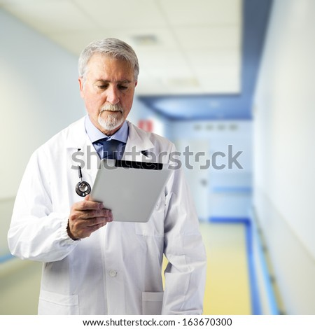 Doctor in the hallway of the hospital with tablet - stock photo