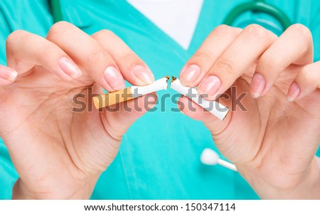 Doctor in uniform breaks cigarette, quit smoking concept, isolated over white - stock photo