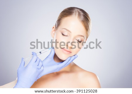 Doctor injecting in a beautiful face of a young woman. Plastic surgery concept. - stock photo