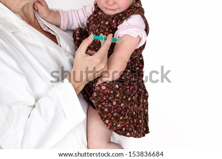 Doctor injects small child in her arms - stock photo