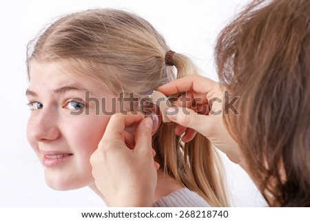 Doctor inserting a hearing aid into a young girl's ear in front of a white background - stock photo